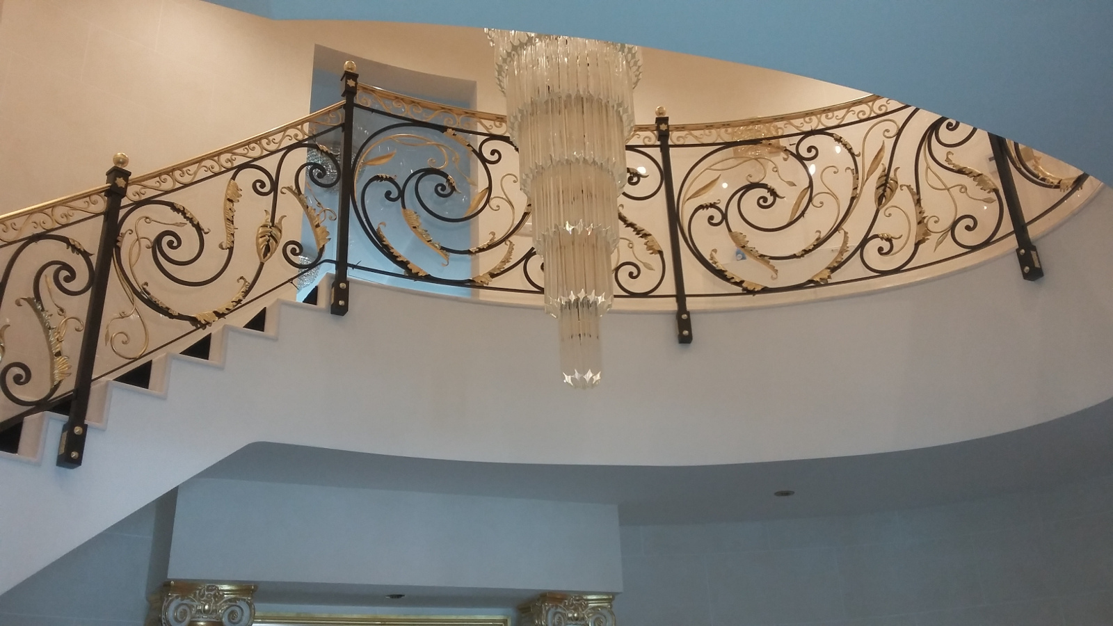 Wrought-iron-staircase-with-decorative-floral-elements-and-handrail-in-mirror-polished-brass-Plexiglas-protection
